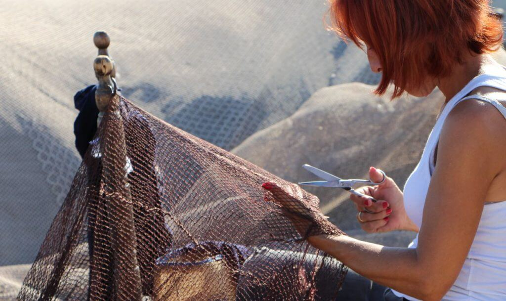 a woman working with fishing nets